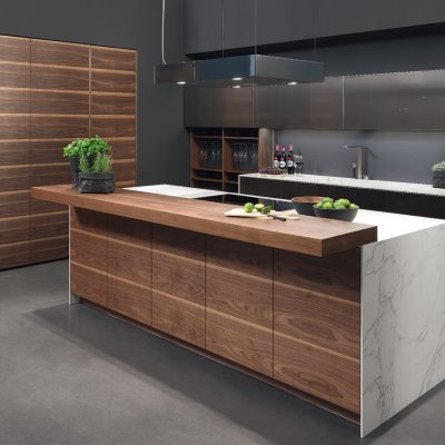 Rational Ino(x): Echt edelstaal en hout. Warme houtsoorten zijn een ideale partner in combinatie met RVS fronten. Walnoot fineer en echte edelstaal fronten vormen een beeld van uitgesproken design